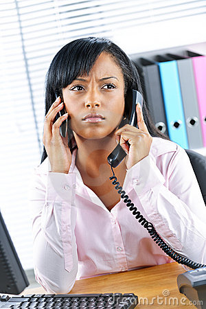 Black businesswoman using two phones at desk
