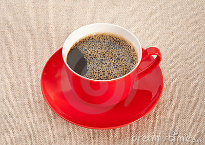 Black coffee in red cup with saucer