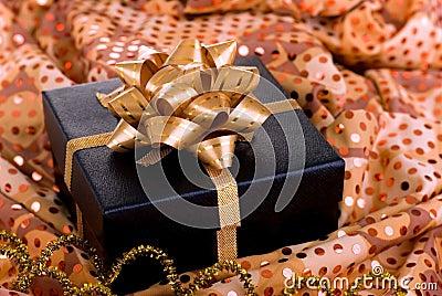 Black gift box with gold ribbon.
