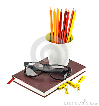 Black glasses and color pencils in white mug placed on notebook.