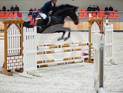 Black horse with rider jumping over obstacle. Riding competition. Editorial Stock Image