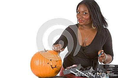 Black make-up artist decorating Halloween pumpkin