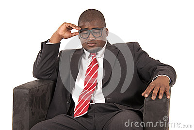 Black male model pondering while sitting is chair wearing a suit