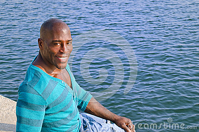 Black man relaxing at the edge of the pool.