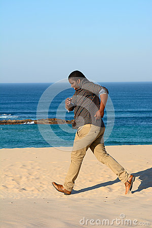 Black man jogging on beach