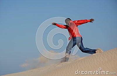 Black man running down dune