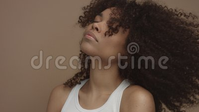 Black model with huge curly hair moving shaking hair in slow motion from 60 fps. Studio shoot stock video footage