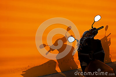 Black motorbike near an orange wall