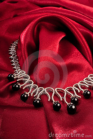 Free Black Pearls On Red Textile Stock Photo - 9927680