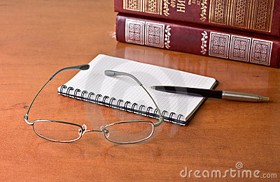 Black pen with notebook and glasses