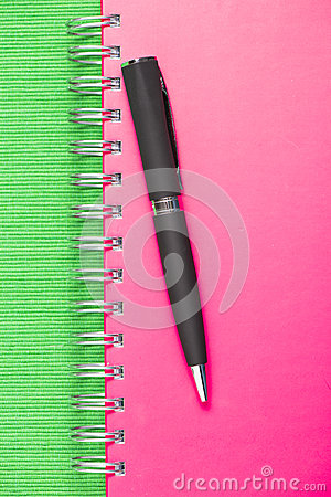 Black pen on pink notebook