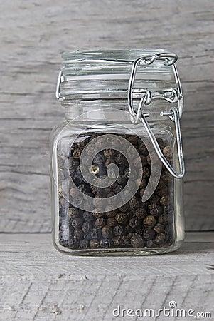 Black peppercorns in jar