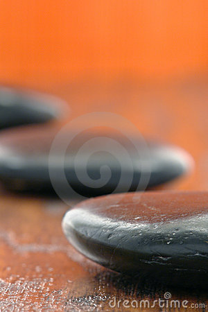 Black polished Hot Massage Stones on Wood in a Spa