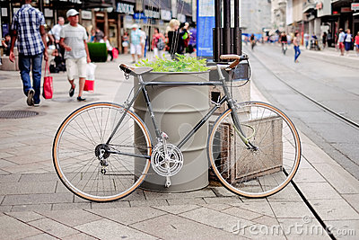 Black Road Bike Leaned On Gray Steel Drum Beside Street With People At Daytime Free Public Domain Cc0 Image