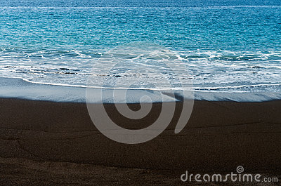 Black sand volcanic beach with white foam sea wave