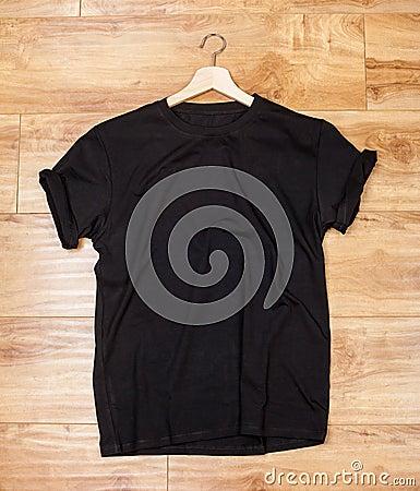 Free Black Shortsleeve Cotton Tshirt On A Wooden Backgronud Stock Photos - 106638643