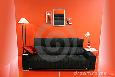 Black sofa on red wall