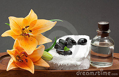 Black spa stones with flowers and essential oil