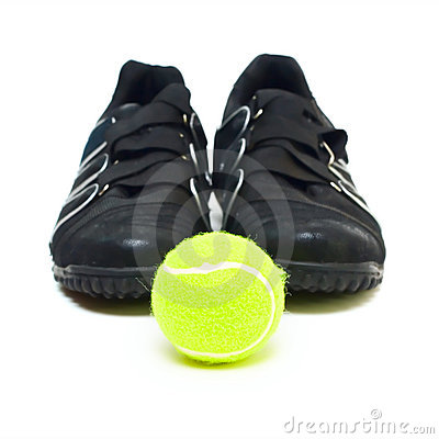Black sport shoes and ball isolated on white