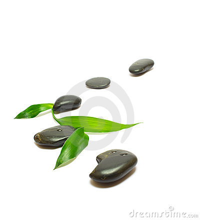 Black stones and bamboo leafs on white