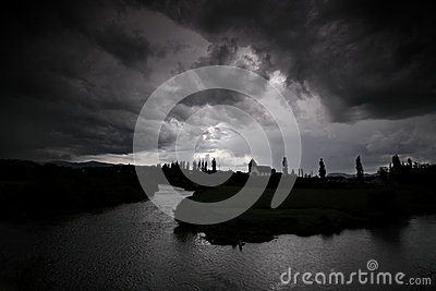 Black storm clouds over a river