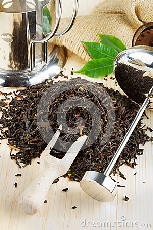 Black tea pile, teapot, wooden scoop