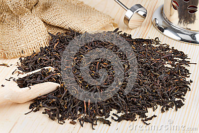 Black tea pile, wooden scoop, teapot