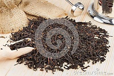 Black tea pile, wooden scoop and teapot