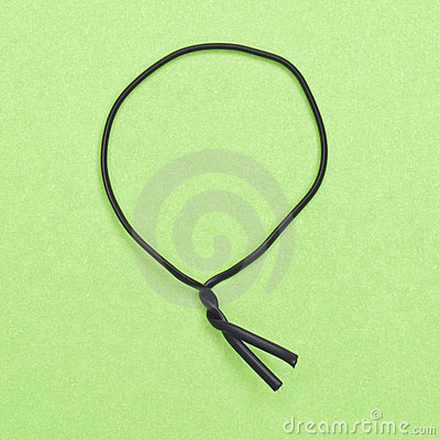 Black Twist Tie on a Green Background.