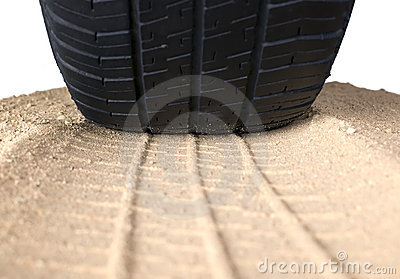 Black tyre and track on sand