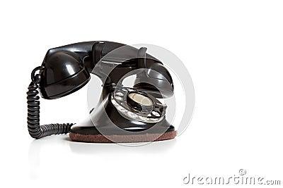 A black vintage telephone on white