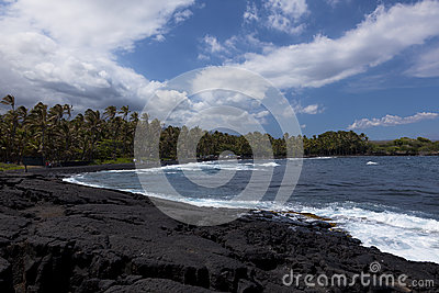 Black volcanic rock forms beach