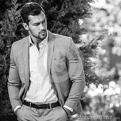Free Black-white Outdoor Portrait Of Elegant Handsome Man In Classical Grey Suit Poses Outdoor Stock Photos - 80762733