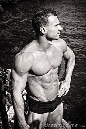 Black and white photo of attractive muscular young man by the sea