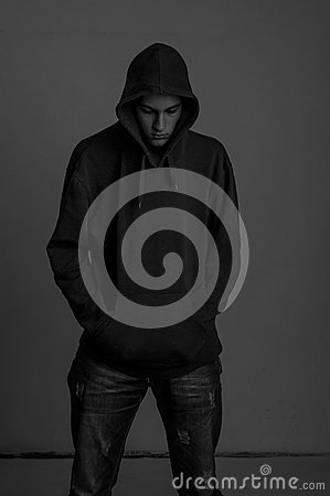 Black and white photo of upsed teenager with hoodie looking down again