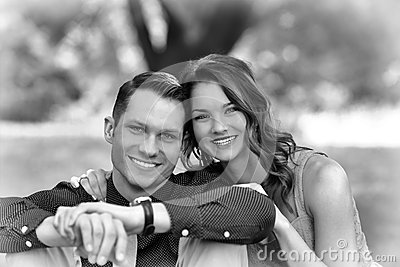 Black and White version of a happy young couple posing seated on