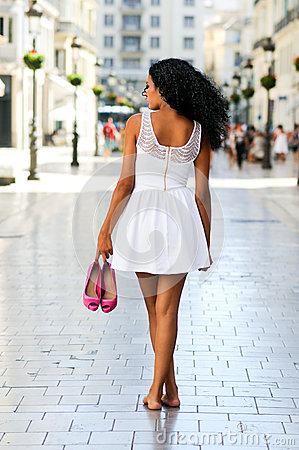 Black woman, afro hairstyle, walking barefoot