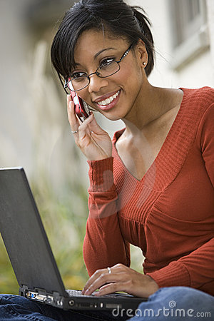 Black woman outside on cell phone and laptop
