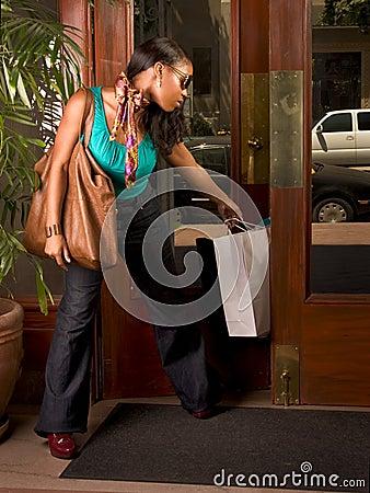 Black woman stuck in door (focus on bag)