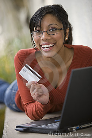 Black woman using credit card and laptop outside