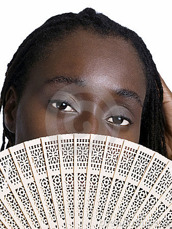 Black woman with wooden fan showing eyes
