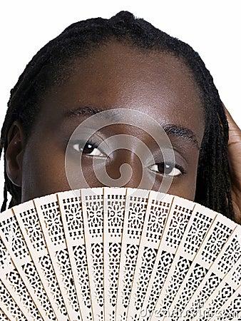 Black woman with wooden fan showing eyes