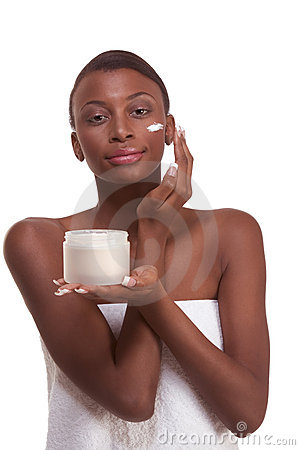 Black woman wrapped in towel moisturizing face