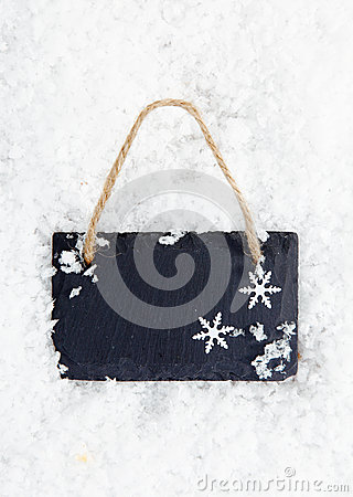 Blackboard on snow with snowflakes