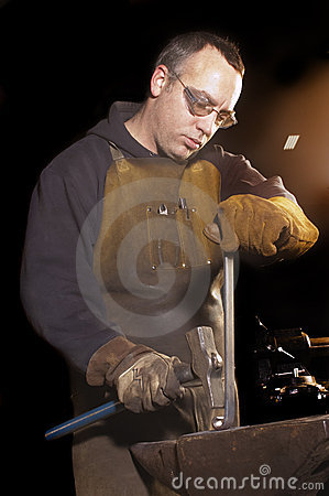 Blacksmith working on decorative handrail