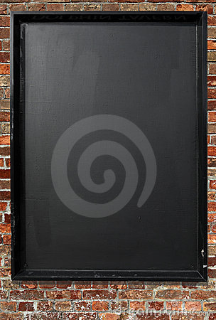 Blank blackboard menu sign on a red brick wall.