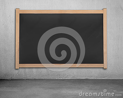 Blank chalk board on concrete wall