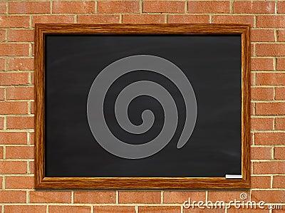 Blank chalkboard on brick