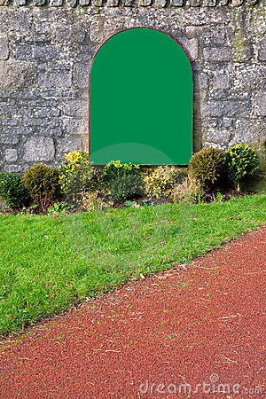 Blank green sign on an old stone wall
