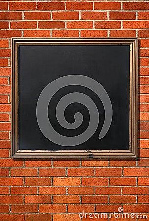 Blank menu blackboard on a brick wall.